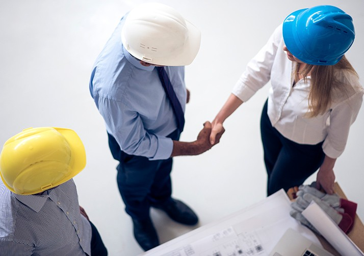 two people wearing hardhats shaking hands