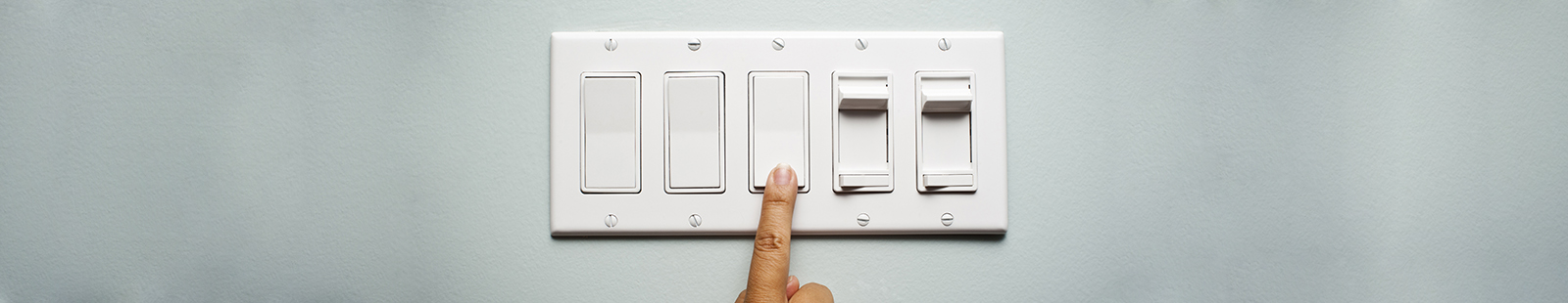 Woman's hand on a light switch showing that she is turning off the power and electricity to conserve energy