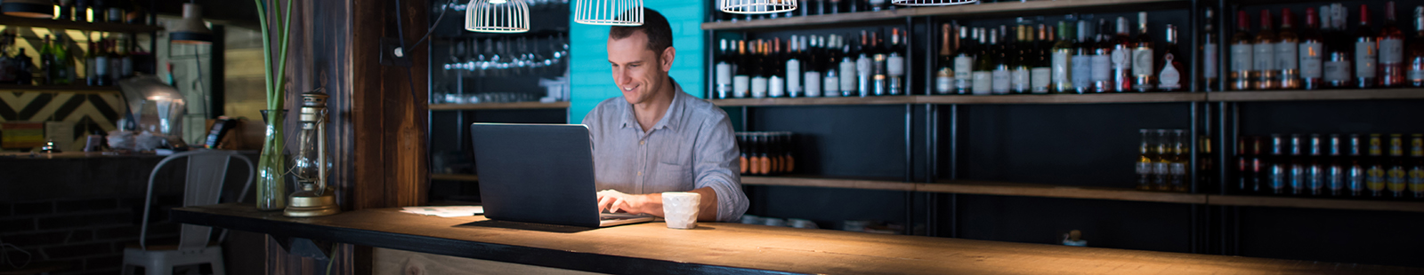 Happy business man working at a restaurant using a laptop computer and doing the books