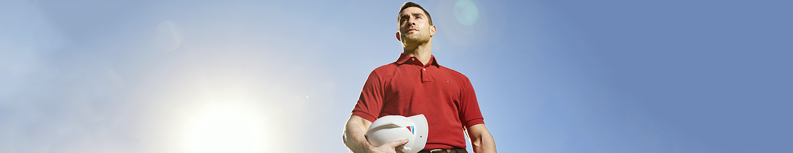 A man in a red shirt holding a hard hat.