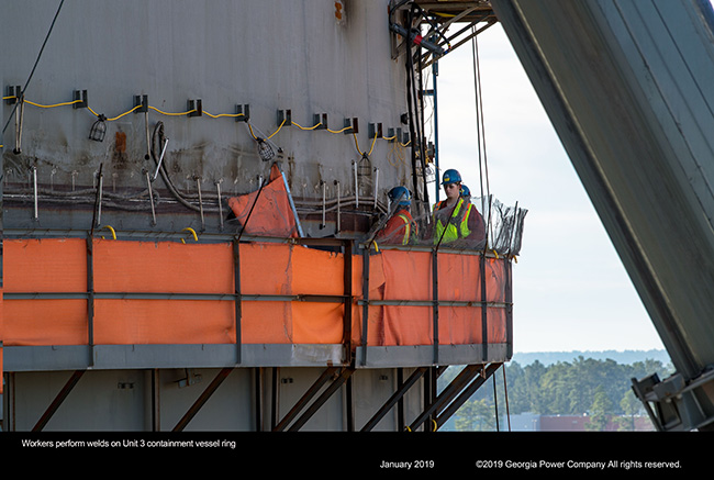 Workers perform welds on Unit 3 containment vessel ring