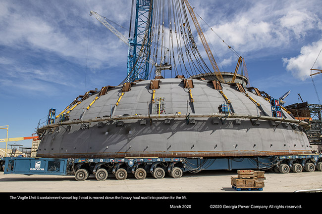 The Vogtle Unit 4 containment vessel top head is moved down the heavy haul road into position for the lift