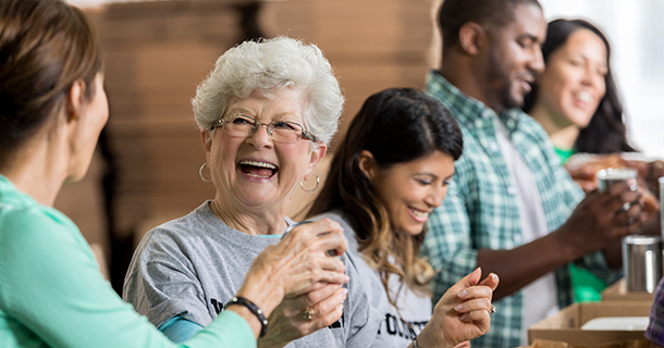 Smiling Caucasian senior woman smiles while accepting a canned food donation at a charity food drive. Volunteers are working in the background.