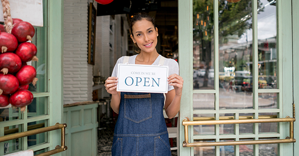 Asian business owner holding an open sign at a restaurant