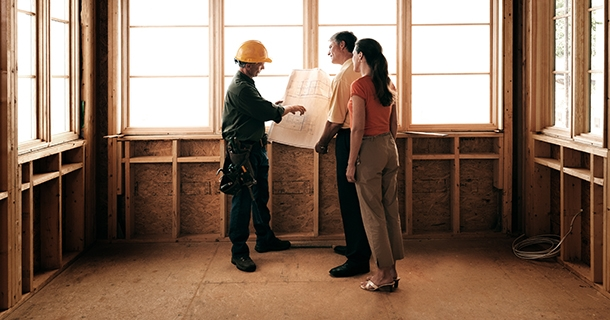 Husband and wife consulting with a architect inside a home under construction.