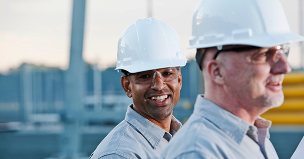 Two men are pictured working at an industrial site.  In the foreground, one man is slightly out of focus with safety goggles on, with a shiny white hard hat and a light blue button-up shirt.  In the middle ground, another man is in focus, smiling at the camera while wearing the same hat and shirt.