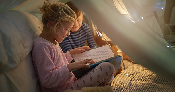 Cropped shot of siblings reading a story under a blanket fort at home