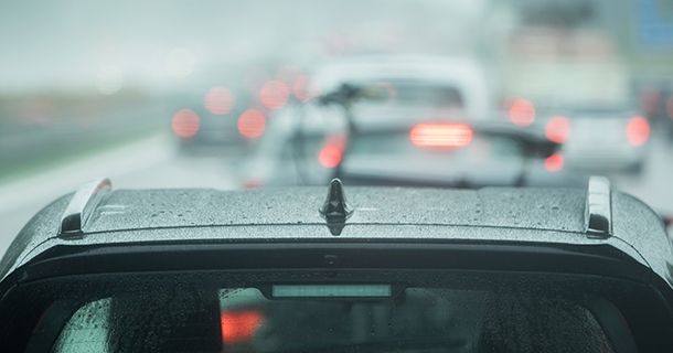 A car is driving on the road in the rain