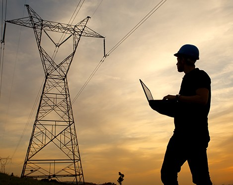 Sihlouette of man with hard hat and computer with a transmission tower in the background