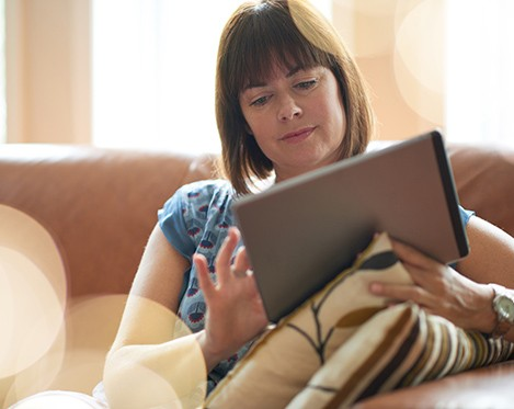 Serene lady in her forties reading emails on a wireless tablet in a brightly lit house- filtered image